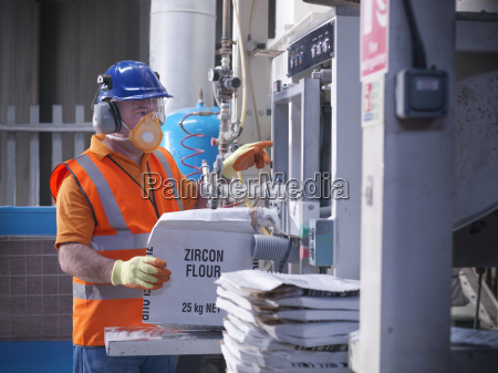 worker in protective clothing filling zircon
