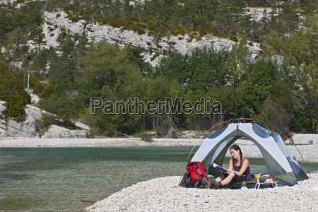 woman in tent by river canyon