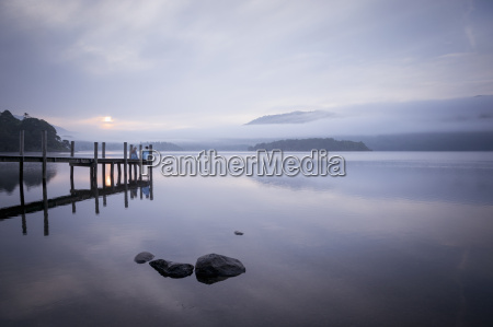 couple on pier by tranquil lake