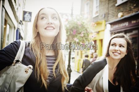 young women walking down street carrying