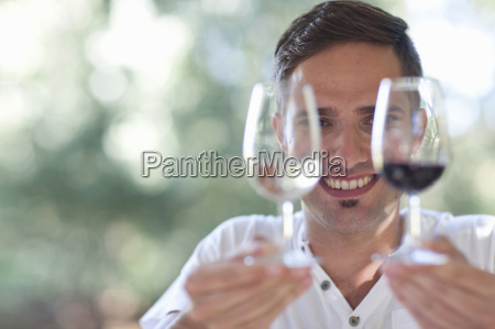 young male waiter holding up glasses