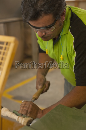 carpenter turning wood with chisel in