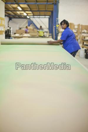 upholsterer unrolling a length of textile