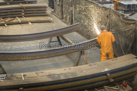 worker grinding metal construction in marine