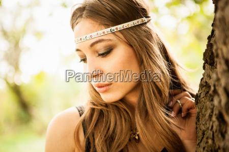 young woman wearing headband looking down