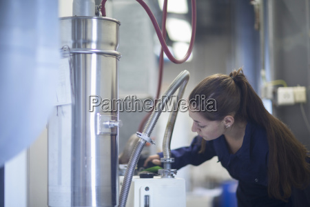 female engineer inspecting industrial piping in