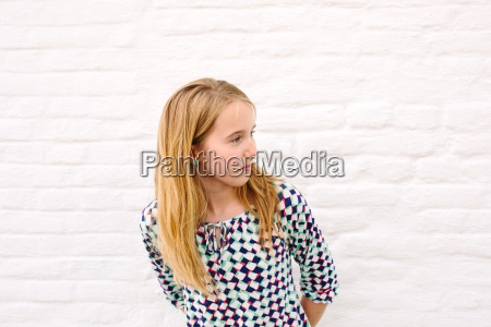 girl leaning forward from white wall