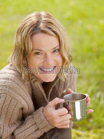 woman holding mug outdoors smiling