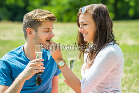 woman feeding grape to her boyfriend
