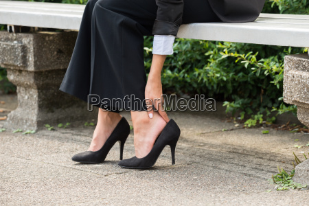 businesswomans hand removing high heels