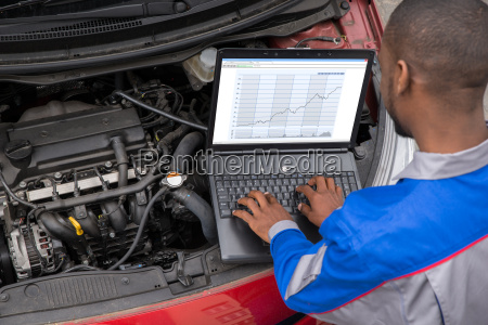 mechanic with laptop while examining engine