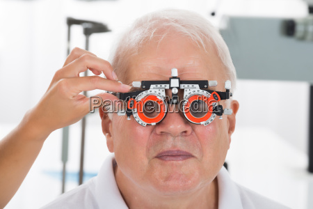 an optometrist checking patient vision with