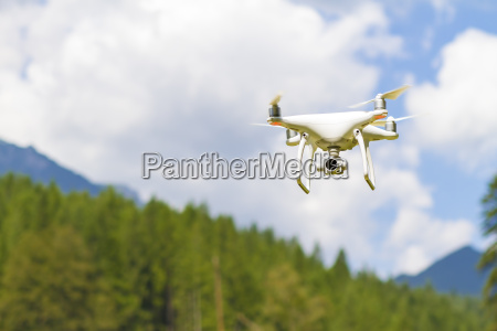 white drone flying above mountains