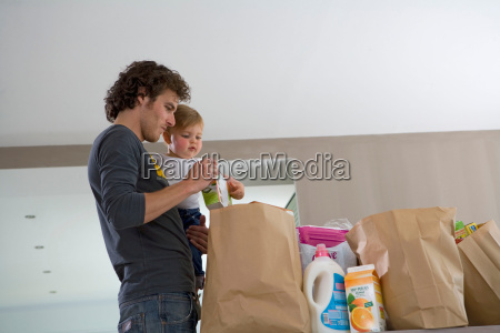 father and baby with grocery bags