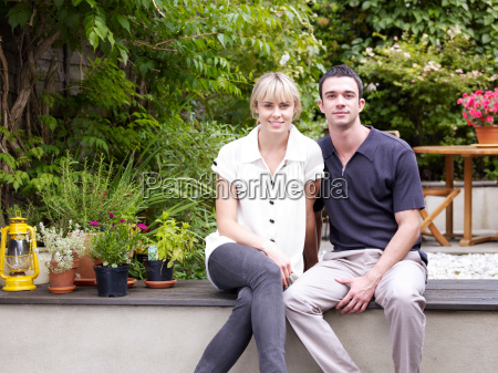 couple sitting in garden facing camera