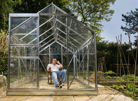 man relaxing in greenhouse with music