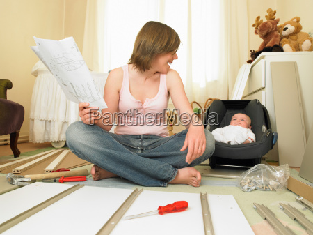 woman and baby building furniture