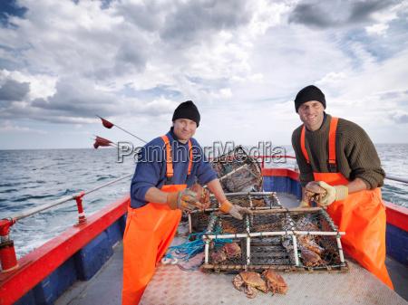 fishermen sort catch of crabs on