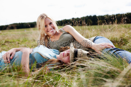 two young women laying in grass