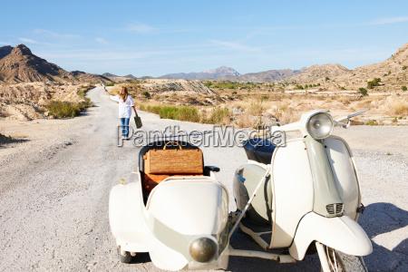 woman walking away from motorbike