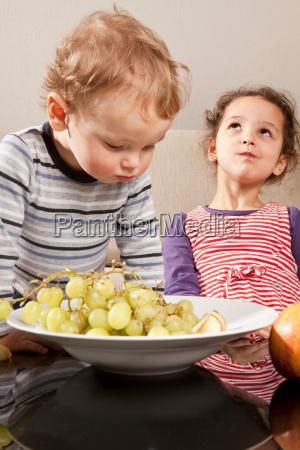 girl and boy eating fruit