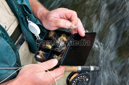 fly fisherman holding fly box in