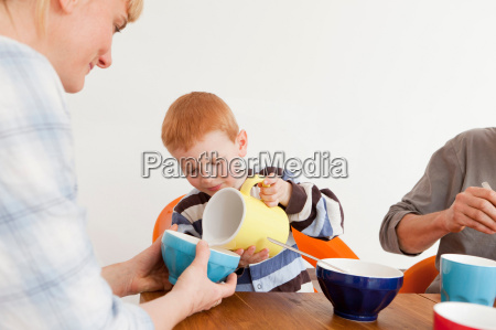 boy pouring milk for mother