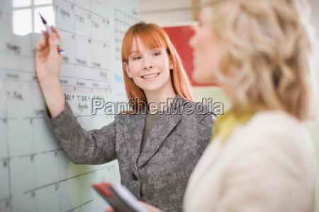 businesswomen writing on calendar