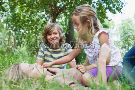mother and children playing in park