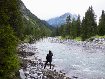 woman taking pictures of a river