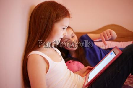 girls using digital tablet together in