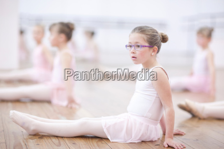 distracted young ballerina sitting on floor