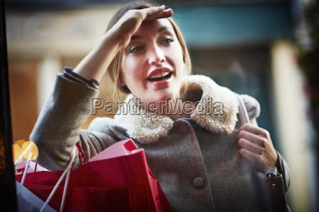 young woman carrying shopping bag looking