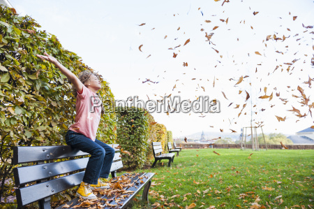 boy sitting scattering leaves into air