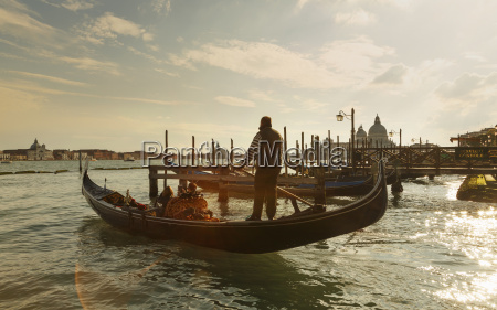silhouetted view of gondolier at sunset