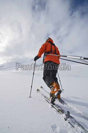 female touring skier pulling an expedition