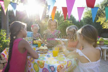 girl serving friends birthday cake