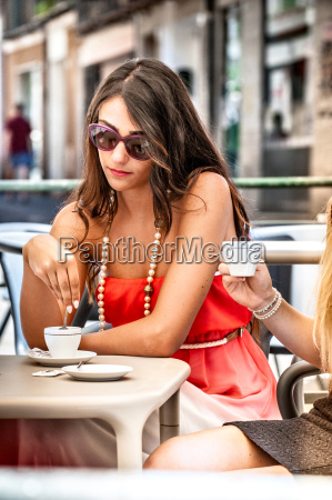 two young female friends drinking espresso