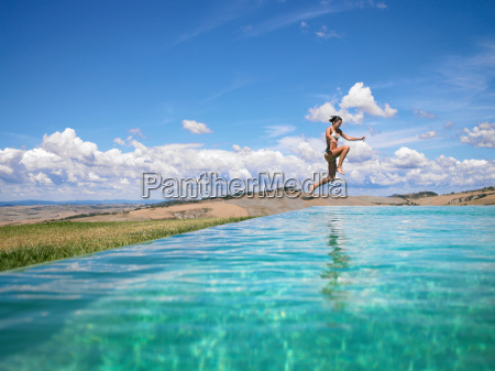 woman jumping in swimming pool