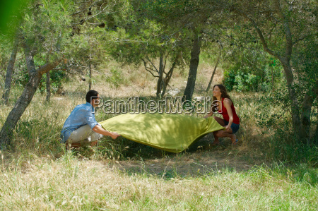 smiling couple laying out picnic blanket