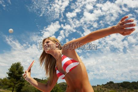 woman in bikini with racket poised