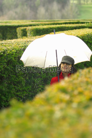 lady with umbrella in maze