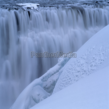 freezing waterfall surrounded by snow