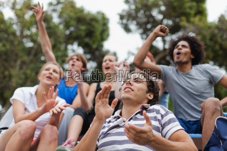 friends cheering at sporting event