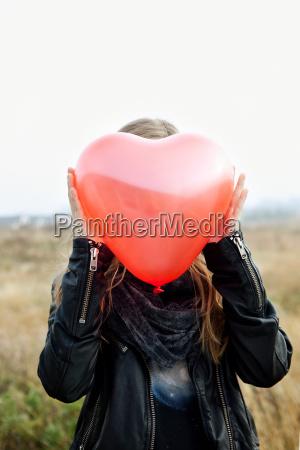 girl holding heart shaped balloon