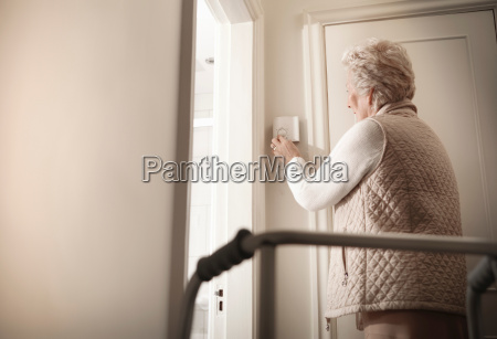 senior woman adjusting thermostat in hallway