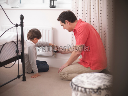 father teaching son to adjust thermostat