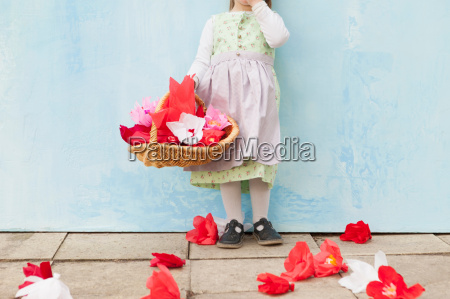 girl holding basket of paper flowers