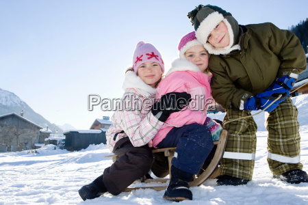 children playing in snow with sledge