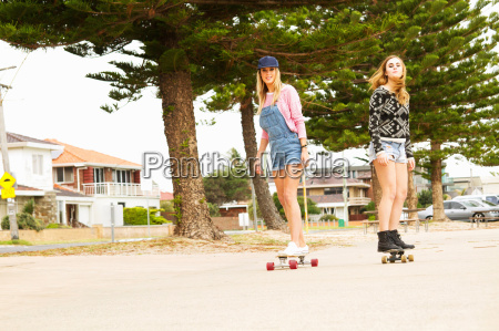 two young women skateboarding through tree